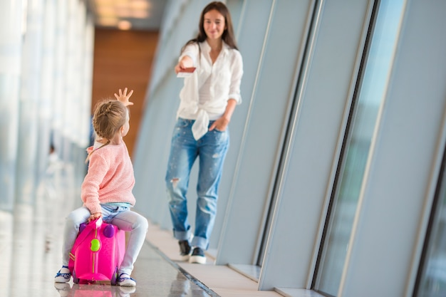 Mother and little girl with boarding pass at airport terminal waiting the flight