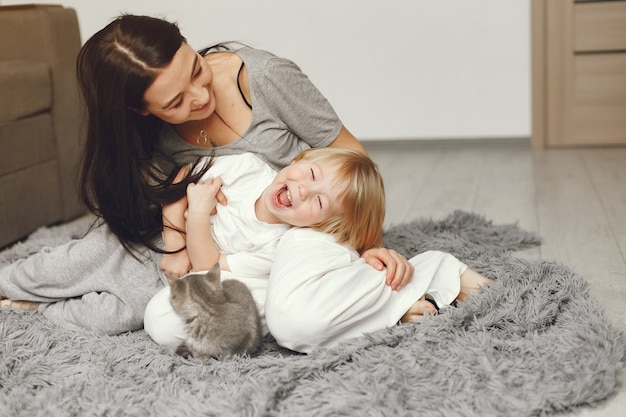 Mother and little son fun at home with a cat