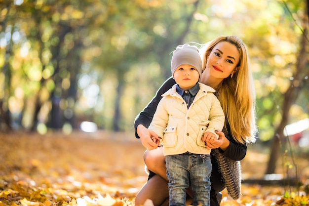 Mother and little son in park or forest, outdoors. hugging and having fun together in autumn park