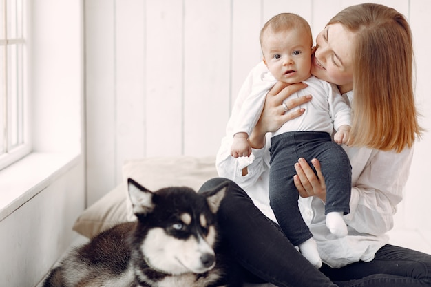 Mother and little son playing with dog at home