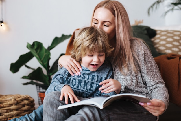 Mother and little son sitting and reading book together at home