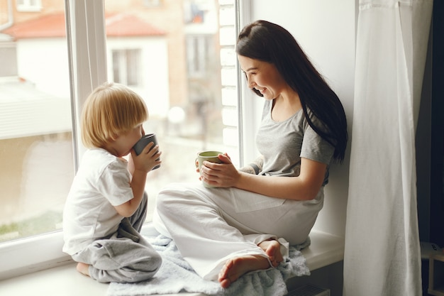 Mother and little son sitting on a windowsill with a tea