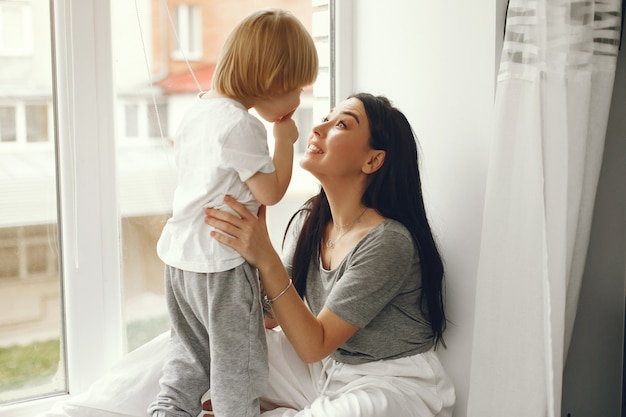 Mother and little son sitting on a windowsill