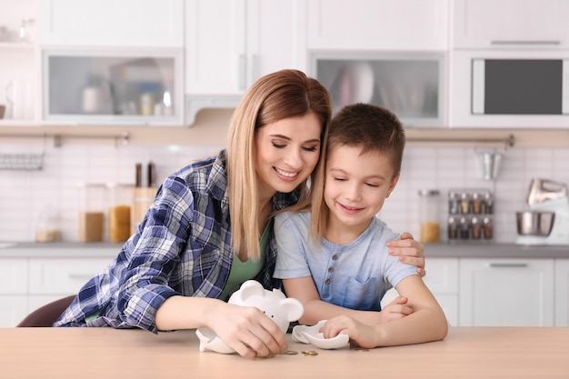 Mother and little son with broken piggy bank on table at home