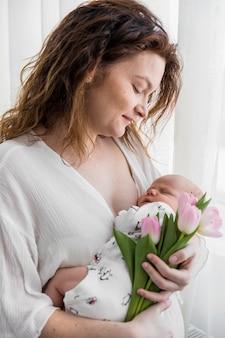 母は自宅でピンクのチューリップの花を持って彼女の赤ちゃんを見て