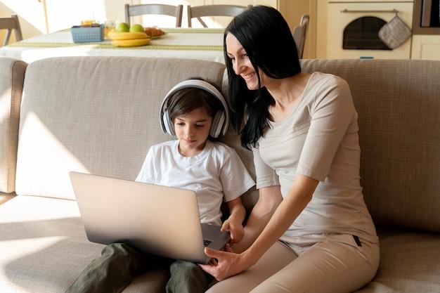 息子がノートパソコンで遊んでいるものを見ている母親