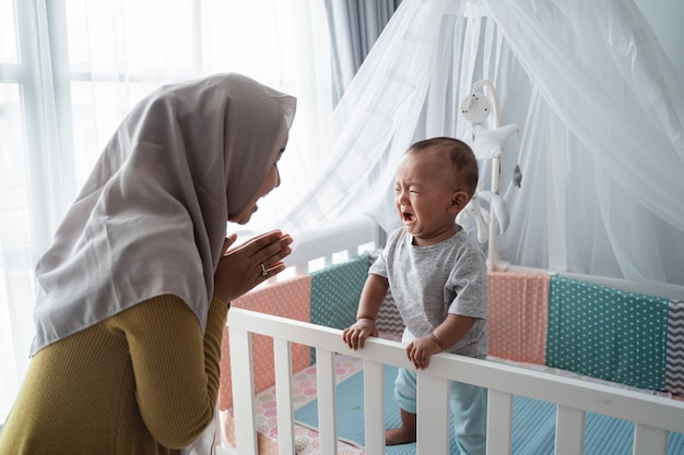 Mother looking at her baby boy crying