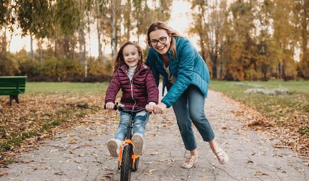 Мама смотрит в очки помогает дочери кататься на велосипеде во время осенней прогулки