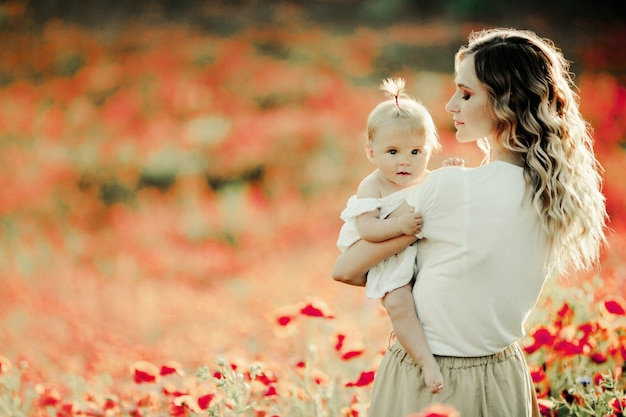 Mother looks at her baby on the poppy field