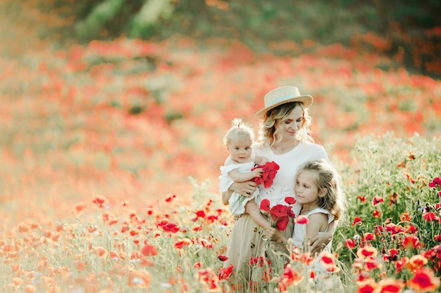 Mother looks at her elder daughter and holds a baby on the poppy field