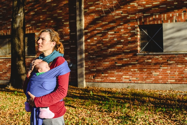 Mother lovingly carrying her newborn baby in a sling scarf during a sunset stroll in front of red brick building.