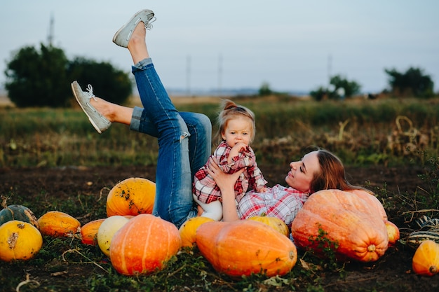 Madre sdraiato su zucche con le gambe e figlia nel suo stomaco