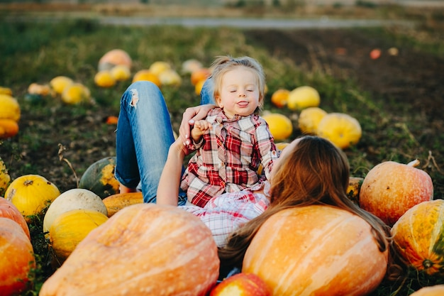 Mother lying on pumpkins with legs up and daughter in her stomach
