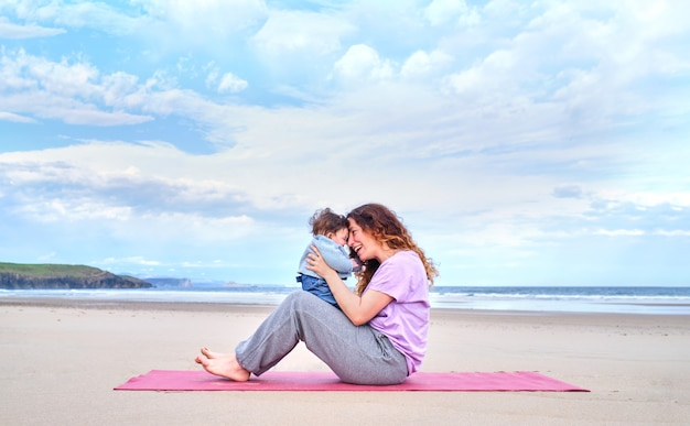 Mother makes gestures of love to her baby sitting on a mat on the beach