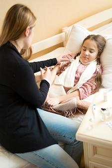 어머니는 침대에 누워 아픈 딸에게 약으로 주사를 만들기