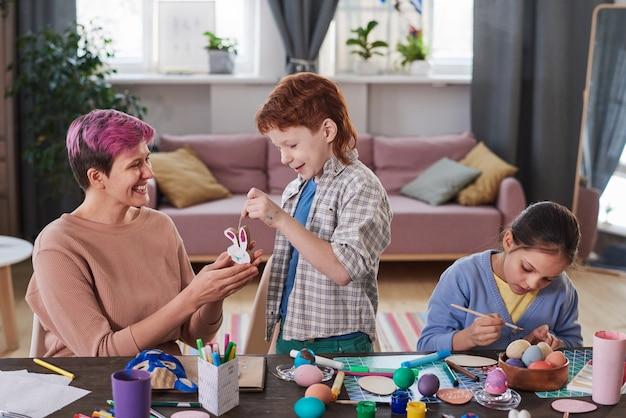 계란을 칠하고 부활절을 준비하는 식탁에서 아이들과 함께 토끼 인형을 만드는 어머니