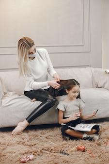 Madre in maschera con la figlia sul pavimento. colorazione della ragazza e madre che la aiutano. Foto Gratuite