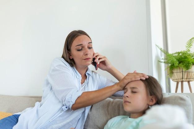 Мать измеряет температуру своего больного ребенка. больной ребенок с высокой температурой лежит в постели, а мать держит термометр. мать с мобильным телефоном звонит врачу