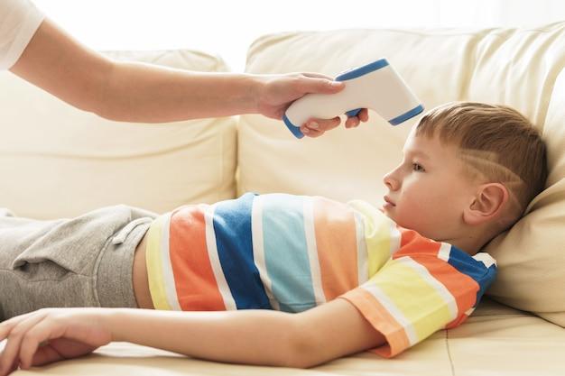 息子の体温を測るお母さん。発熱はインフルエンザやその他のウイルスの症状です。