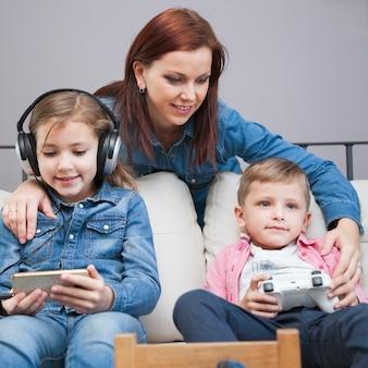 Mother near kids using technologies