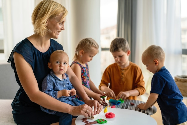 Mother or nursery teacher teaches her children to work with colorful play clay toys. children creativity concept