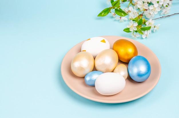 コピースペースと青い背景の上のプレート上のイースターの真珠色の卵の母。季節性のコンセプト、春、はがき、休日。フラットレイ、テキストの場所。閉じる。