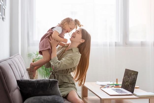 Мать на диване держит девочку