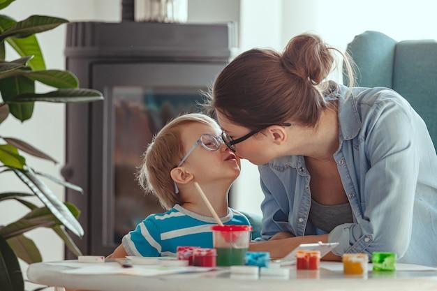 母または子が家で一緒にキスして水彩絵の具を描く