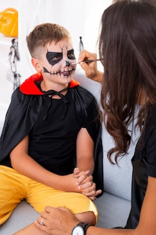 Mother painting her sons face for halloween