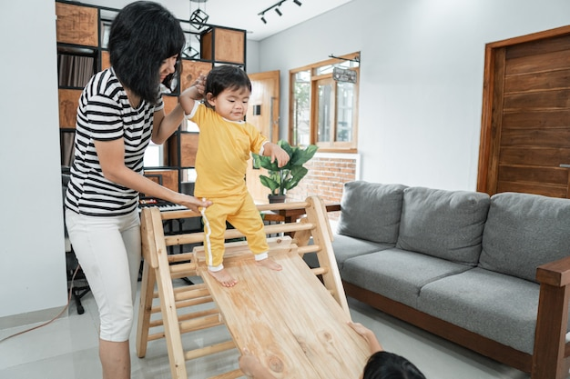 A mother patiently holds the babys hand while standing sliding on a pikler triangle toy at home