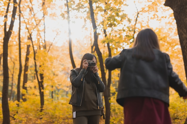 어머니 사진 작가는 가을 공원에서 딸의 사진을 찍습니다. 취미, 사진 예술 및 여가 개념.