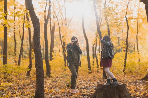 母の写真家は秋の趣味の写真アートと公園で彼女の娘の写真を撮ります