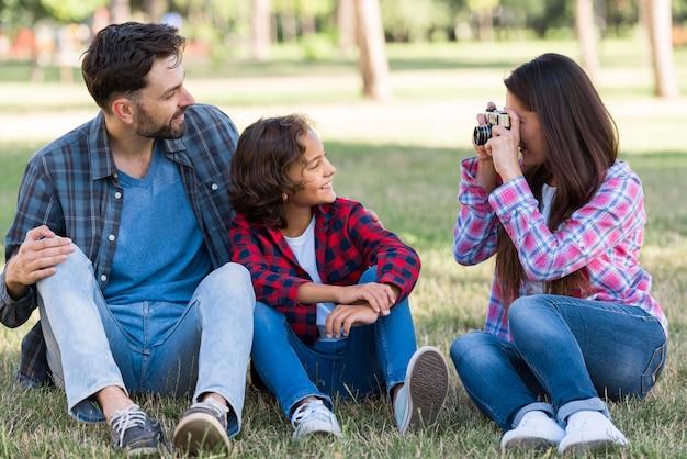 Мать фотографирует отца и сына на открытом воздухе в парке