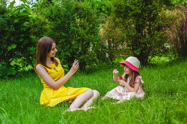 Мать фотографирование ее дочь в то время как дует мыльные пузыри