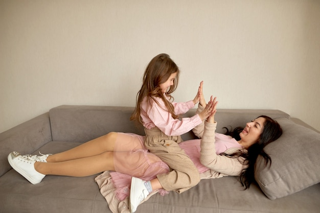 Mother play with daughter in kids game. happy childhood. spend time together at home