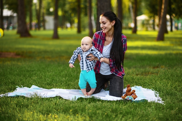여름 공원에서 잔디에 그녀의 작은 아기와 어머니 놀이