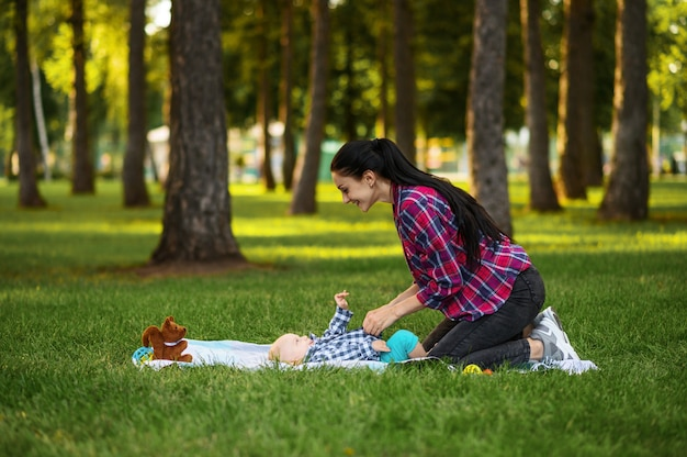 여름 공원에서 잔디에 그녀의 작은 아들과 어머니 놀이