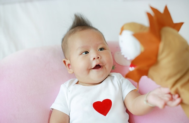 Mother playing animal puppet with her infant baby boy on the bed room