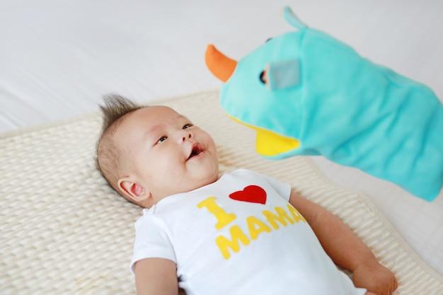 집에서 침대 방에 그녀의 유아 아기와 함께 동물 인형극을 연주 어머니.
