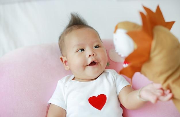 침대 방에 그녀의 유아 아기와 함께 동물 인형극을 재생하는 어머니