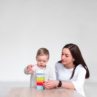Mother playing with baby at home with copy space