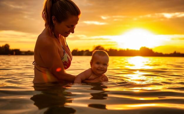 일몰 동안 물에서 아기와 함께 노는 어머니.