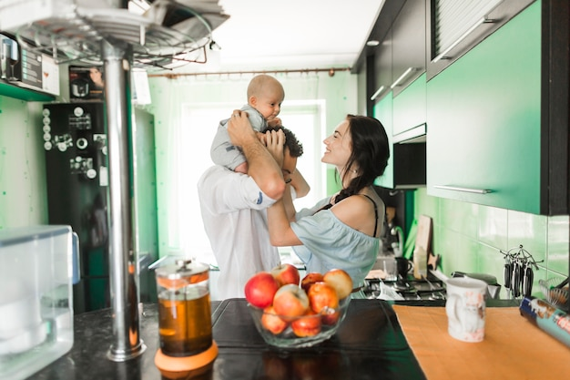 Mother playing with baby sitting on man's shoulder standing in the kitchen