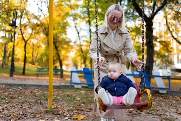 Mother playing with baby on swing