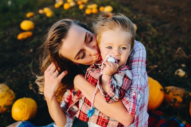 Madre che gioca con sua figlia in un campo con le zucche