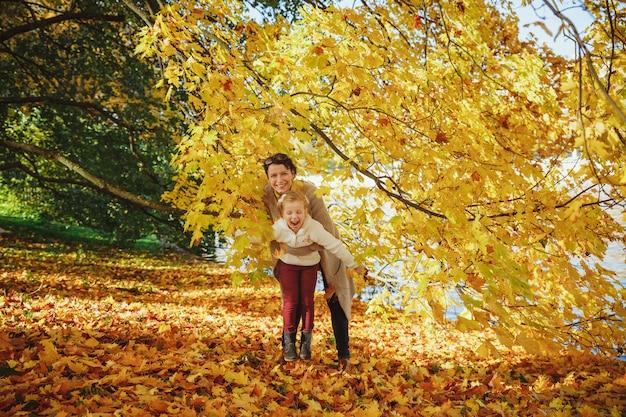 Мать, играя со своей дочерью в парке. мама и ее ребенок, играя вместе на осень прогулка на свежем воздухе. модная семейная концепция - стильная одежда матери и ребенка.