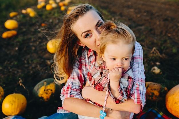 Мать играет со своей дочерью на поле с тыквами
