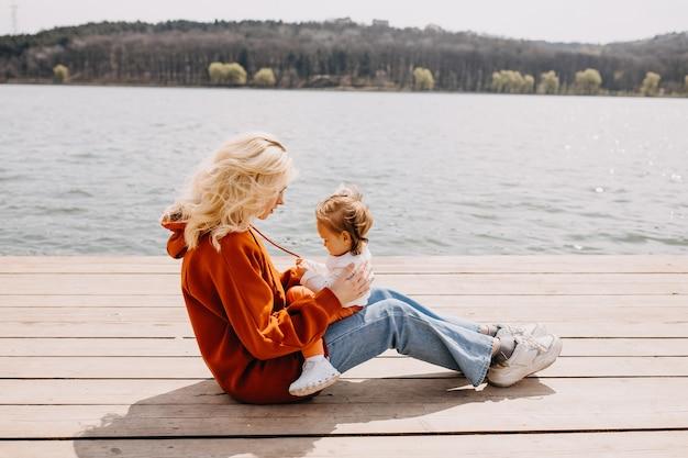 湖のそばの木の桟橋に座って屋外で娘と遊ぶ母