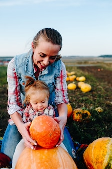 Mother playing with her daughter with pumpkins