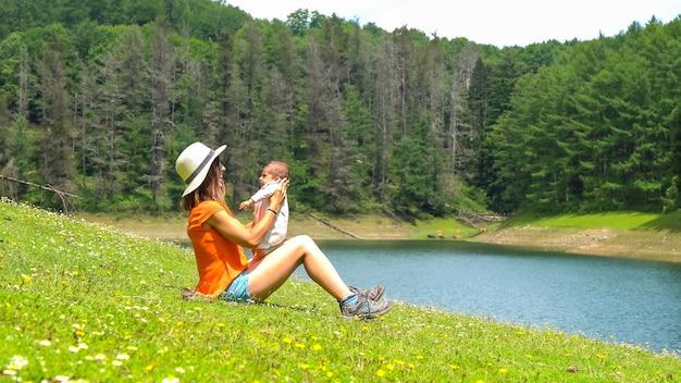 周りに松の木と美しい花が咲く湖で生まれたばかりの息子と遊ぶ母